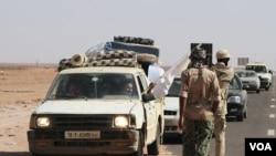 Seorang laki-laki nampak sedang melambaikan bendera putih kepada petugas yang akan memeriksa kendaraan dan muatannya di pos-pos penjagaan menuju Sirte, Libya (28/8).