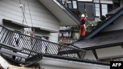 22일 지진으로 내려 앉은 나가노현 가옥 위에 주민 한명이 올라서 있다.