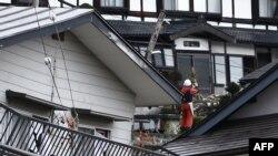Seorang warga berdiri di tengah-tengah rumah-rumah yang rusak akibat gempa bumi yang mengguncang, di Hakuba, sekitar 300 km dari Tokyo, 23 November 2014.