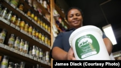 An assistant at the Fresh Earth store in Johannesburg, Kgomotso Mphshe, holds a product she sells regularly: natural, organic yoghurt produced by farmer Elizabeth Aymes and her workers.
