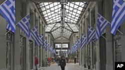 Pedestrian walk inside an arcade full of Greek flags in central Athens, on Wednesday, March 14, 2012.