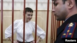 FILE - Ukrainian military pilot Nadezhda Savchenko stands inside a defendants' cage as she attends a court hearing in Moscow, April 17, 2015.