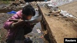 Một bé trai uống nước gần một dòng suối ở quận Fuyuan trong tỉnh Vân Nam, Trung Quốc.