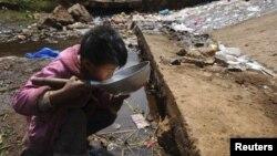 Một bé trai uống nước gần một dòng suối trong quận Fuyuan, tỉnh Vân Nam, Trung Quốc. Nhiều quốc gia ở Á Châu đang đối mặt với mối rủi ro xảy ra một vụ khủng hoảng nước nếu họ không giải quyết được sự quản lý yếu kém có thể dẫn tới tình trạng thiếu nước sạch nghiêm trọng.