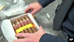 A US customs agent unwraps a box of illegal Cuban cigars that will be destroyed, Dec 2010
