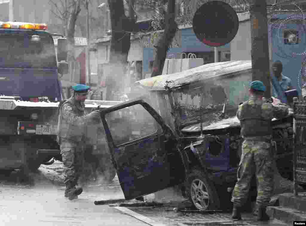 Turkish soldiers take pictures of a vehicle at the site of a suicide attack in Kabul, Feb. 26, 2015.