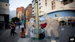 FILE - A sculpture of oil workers — figures who represent an industry critical to Venezuela's economic well-being — decorates a sidewalk in Caracas, Oct. 23, 2014.