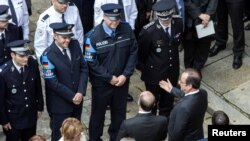 Le président français François Hollande et son ministre de l'Intérieur Bernard Cazeneuve lors de la cérémonie d'hommage au policier Jean-Baptiste Salvaing et sa femme, agent administratif Jessica Schneider, tués à coup de couteau par Larossi Abballa, à Paris, France, le 15 juin 2016.