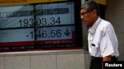 Seorang pria berjalan melewati papan elektronik yang menunjukkan angka perdagangan indeks saham Nikkei di luar sebuah perusahaan pialang di distrik bisnis di Tokyo, 29 Agustus 2017.