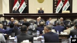 FILE - Iraqi Prime Minister Haider al-Abadi, center, attends a session of the Iraqi Parliament, in Baghdad, Iraq, Sept. 27, 2017. Iraq's Kurdish lawmakers are reportedly ending to their boycott of the national parliament.