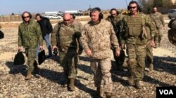 Gen. Frank McKenzie, center front, the top U.S. commander for the Middle East, walks as he visits a military outpost in Syria, Saturday, Jan. 25, 2020.
