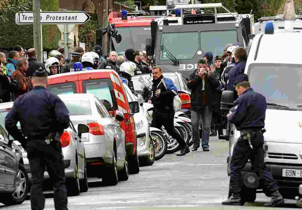 Polisi terlihat di kompleks perumahan Belle Paule saat berupaya menangkap Merah, tersangka pelaku penembakan di Toulouse (AFP).
