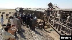 Para petugas, regu penolong dan warga setempat berkumpul di sekitar kereta penumpang yang anjlok akibat serangan bom di provinsi Baluchistan, Pakistan (21/10).