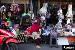 Seorang pedagang di pasar tradisional mengenakan masker sambil menunggu pelanggannya, saat pemerintah melonggarkan pembatasan darurat di tengah pandemi COVID-19 di Jakarta, 26 Juli 2021. (REUTERS/Willy Kurniawan)