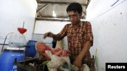 Hamidi menaruh limbah plastik ke dalam kotak besi sebelum membakar dan mengubahnya menjadi bahan bakar di TPA Rawa Kucing, Tangerang, Banten (17/3). (Reuters/Beawiharta)