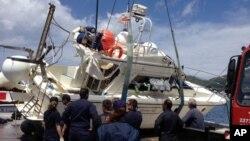 Cảnh sát biển chuẩn bị kéo chiếc thuyền chở di dân bị lật lên bờ tại cảng Vathy trên đảo Samos của Hy Lạp, ngày 5/5/2014.