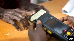 An elderly Nigerian woman validates her voting card using a fingerprint reader, prior to casting her vote later in the day, in the home town of opposition candidate Gen. Muhammadu Buhari, in Daura, Nigeria, March 28, 2015.
