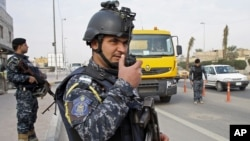 Iraqi federal policemen stand guard at a checkpoint in Basra Jan. 2, 2014. The Iraqi government has tightened security measures after security forces reportedly arrested al-Mukhtar Army commander, Wathiq al-Batat.