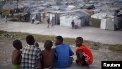 Sekelompok bocah laki-laki duduk di atas atap rumah yang hancur karena gempa Haiti 2010, di seberang sebuah kamp yang mereka tinggali di Port-au-Prince, Januari 2013. (Foto: Dok)