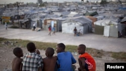 ພວກເດັກນ້ອຍເຮຕີຈຸນຶ່ງ ພາກັນນັ່ງຢູ່ເທິງຫຼັງຄາເຮືອນ ທີ່ໄດ້ຮັບຄວາມເສຍຫາຍ ຈາກແຜ່ນດິນໄຫວໃນປີ 2010 ຊຶ່ງຕັ້ງຢູ່ຕໍ່ໜ້າສູນ ທີ່ພວກເຂົາເຈົ້າອາໄສຢູ່ ໃນເວລານີ້ ທີ່ນະຄອນຫຼວງ Port-au-Prince (9 ມັງກອນ 2013)