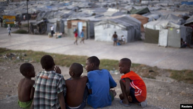 A group of boys sit on the rooftop of a home damaged by the 2010 earthquake, across from a camp where they now reside, Port-au-Prince, Haiti, January 9, 2013.