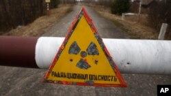 """Một tấm biển với hàng chữ """"bức xạ nguy hiểm"""" tại làng Babchin, gần khu vực 30 km xung quanh lò phản ứng hạt nhân Chernobyl. Mỗi năm có hàng ngàn du khách đi thăm Chernobyl, và con số đó còn gia tăng. Tạp chí Forbes gọi đây là 'nơi du lịch kỳ lạ nhất trên trái đất'."""