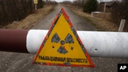 "FILE - A sign reads ""Radiation danger"" in the village of Babchin, near the 30 km exclusion zone around the Chernobyl nuclear reactor, March 22, 2011."