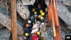 救援人员2月7日从台南大地震倒塌的建筑中搬运出一具尸体。