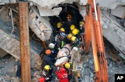 FILE - Emergency rescuers remove a body found in a collapsed building from an earthquake in Tainan, Taiwan, Feb. 7, 2016.