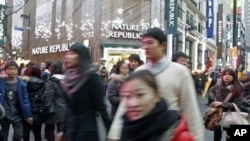 Koreans go about their business in central Seoul, South Korea, December 19, 2010.