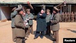 ທ່ານ Kim Jong Un (ກາງ) ຜູ້ນໍາເກົາຫລີເໜືອ ຢ້ຽມຢາມ ໜ່ວຍຍິງປືນໃຫຍ່ໄລຍະໄກ ຂອງກອງທັບປະຊາຊົນ ເກົາຫລີເໜືອ ເລກທີ 641 ໃນວັນທີ 11 ມີນາ 2013