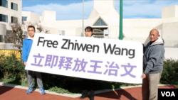 活动人士在中国驻华盛顿大使馆外示威要求中国释放法轮功学员。(2014年10月24日,美国之音拍摄)