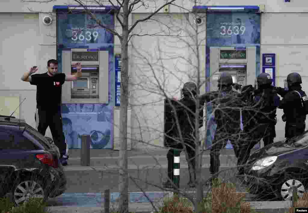 A suspect in a hostage taking situation raises his arms in the air as he is detained by members of special French RAID forces outside the post offices in Colombes outside Paris, Jan. 16, 2015.