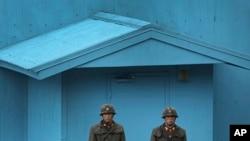 ທະຫານເກົາຫຼີເໜືອ ຢືນຍາມບ້ານສະຫງົບເສິກແຫ່ງ Panmunjom ທີ່ເຂດປອດທະຫານ DMZ ເຊິ່ງແບ່ງແຍກ ສອງປະເທດເກົາຫຼີ ອອກຈາກກັນ.