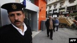 Kahire'de bir bankanın güvenlik görevlisi yeniden açılan bankanın önünde beklerken