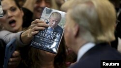 FILE - A woman thrusts Republican Donald Trump's book at him for an autograph at his campaign rally in Manassas, Virginia, Dec. 2, 2015. Trump said at the time that his plan for combating Islamic State militants involved targeting not just the group's fighters but also their families.