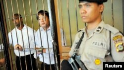 FILE - Australian death row prisoners Andrew Chan, center, and Myuran Sukumaran, left, are seen in a holding cell waiting to attend a review hearing in the District Court of Denpasar on the Indonesian island of Bali, October 8, 2010.