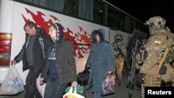 Members of pro-Russian rebels walk past Ukrainian servicemen during an of exchange of prisoners of war outside Donetsk, Ukraine, Dec. 26, 2014.