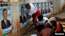 Supporters paste campaign posters of Madagascar's presidential candidate Robinson Jean-Louis along the streets of the capital, Antananarivo, October 23, 2013.