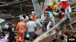 Tim penyelamat dan warga sekitar mengangkat korban dari longsoran tanah akibat hujan deras di Manizales, Kolombia (5/11).