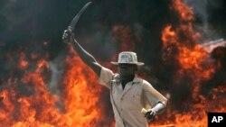 Mfuasi wa chama cha Orange Democratic Party ODM akibepa panga mbele ya kizuizi kinachowake moto wakati wa ghasia za 2008 katika kitongoji cha Kibera Nairobi.