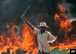 FILE - A supporter of the Orange Democratic Party holds up a machete in front of a burning barricade during riots in the Kibera slum in Nairobi, Kenya, Dec. 29, 2007.
