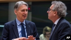Britain's Chancellor of the Exchequer Philip Hammond, left, talks with Luxembourg's Finance Minister Pierre Gramegna during a round table meeting of EU finance ministers at the EU Council building in Brussels on Jan. 27, 2017.