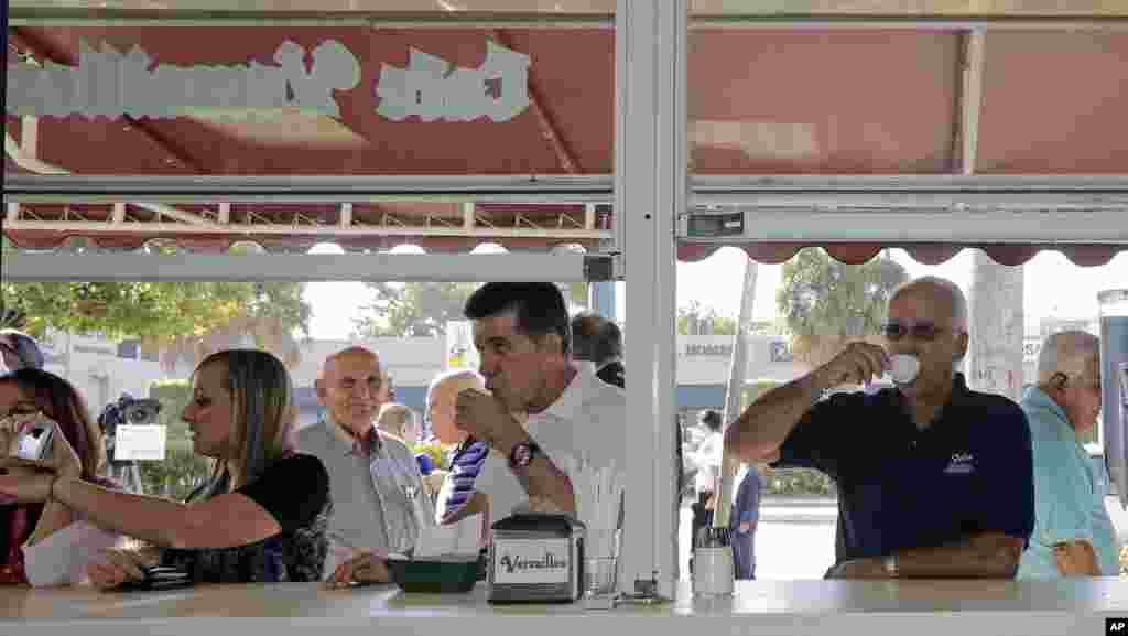Cuban-American Jose Feliu (right) enjoys a Cuban coffee as he prepares to go to work in the Little Havana area of Miami, Dec. 18, 2014.