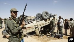 A Tunisian army soldier stands guard near an overturned car which belongs to forces loyal to Libyan leader Moammar Gadhafi after clashes with Tunisians and rebel fighters in Dehiba near the Libyan and Tunisian border crossing of Dehiba, April 29, 2011