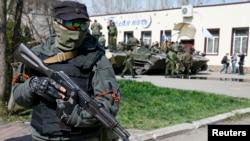 一名戴面罩的亲俄抗议者持枪站立在斯洛文斯克,他的身后是装甲运兵车。(2014年4月16日)