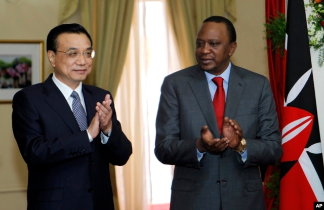 FILE - Chinese Premier Li Keqiang, left, and Kenya's President Uhuru Kenyatta applaud after the signing of the Standard Gauge Railway agreement with China at the State House in Nairobi.