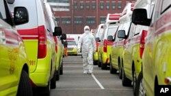Radnik u zaštitnom odelu pored vozila za prevoz pacijenata obolelih od koronavirusa u Južnoj Koreji