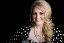 """American singer, songwriter and record producer known for the pop single """"All About That Bass"""" Meghan Trainor poses for a portrait, on Aug. 7, 2014 in New York."""