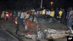 Warga berkumpul di dekat sebuah mobil yang hancur karena ledakan bom di Abuja, Nigeria (1/5).